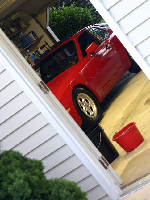 garage filled with a red sports car and household items on shelves