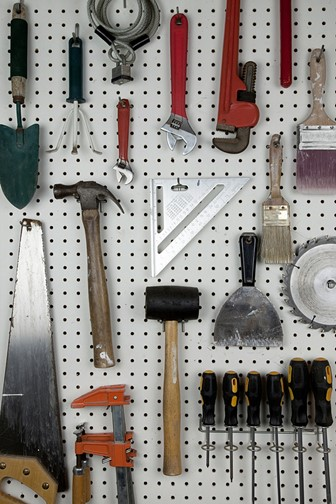 assorted tools hanging on a garage pegboard